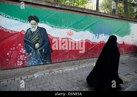 veiled Iranian woman, walks past a Ayatollah Khomeini's picture painted on a wall of the former US Embassy in Tehran, - Stock Photo