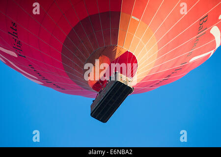 Red Virgin hot air balloon flight passing low with a basket of passengers and a deep blue late evening sky in the - Stock Photo