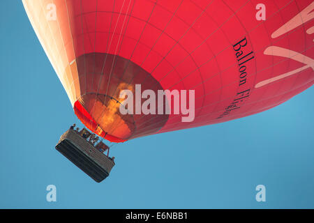 Red Virgin hot air balloon flight passing low with a basket of passengers and igniting the burners against a deep - Stock Photo