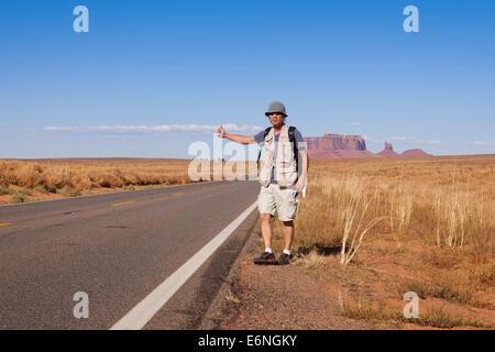 Man hitchhiking on rural desert highway - Utah USA - Stock Photo