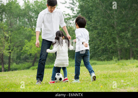 Happy father and children playing football together - Stock Photo