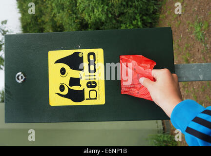 A hand grabs a plastic bag for dog dirt near Altglashuetten in the Black Forest, July 29, 2014. Photo: Wolfram Steinberg - Stock Photo