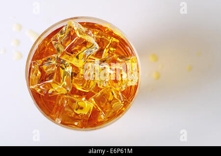 Top view on alcoholic drink in a glass with ice cubes and spilled drops on the table - Stock Photo