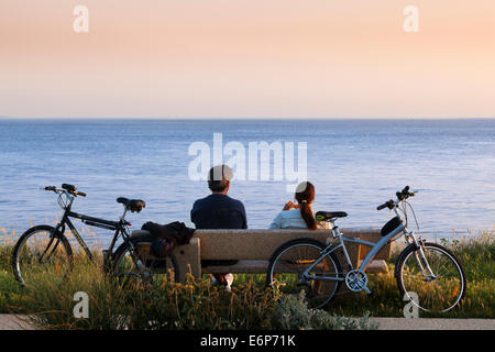 Two cyclists rest on a bench to watch the evening sky over the sea. - Stock Photo