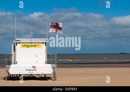 Lifeguard station flying RNLI flag, on a deserted British beach. - Stock Photo