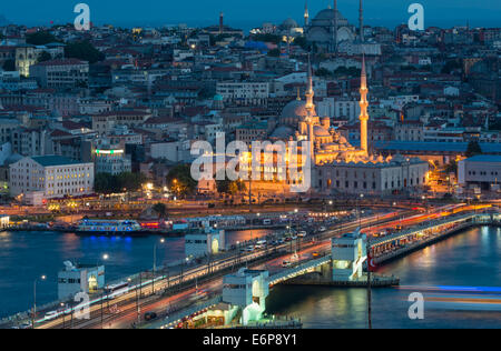 Yeni Cami (New Mosque) lit up at night, with Galata Bridge in the foreground. - Stock Photo