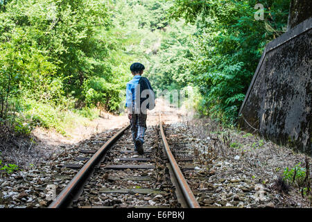 Child walking on railway - Stock Photo