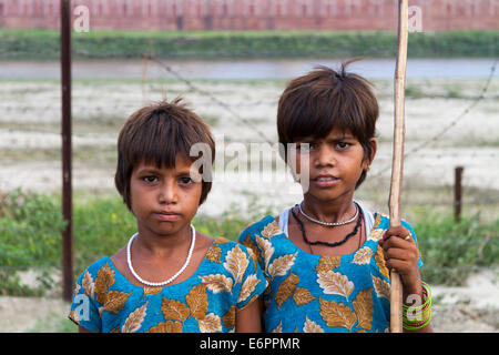 Close up of two identically dressed young Indian girls, smiling, by the Jamuna River near the Taj Mahal in Agra - Stock Photo