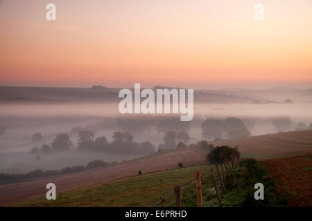 Autumn mist in the Wylye Valley, Wiltshire, England, photographed from Ebsbury Hill near the village of Great Wishford. - Stock Photo