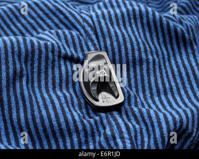 Close up of store security tag on clothing used to prevent theft - Stock Photo