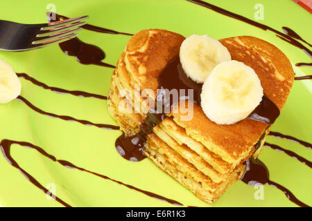 Banana pancakes and chocolate sauce on a paper plate/ tray ...