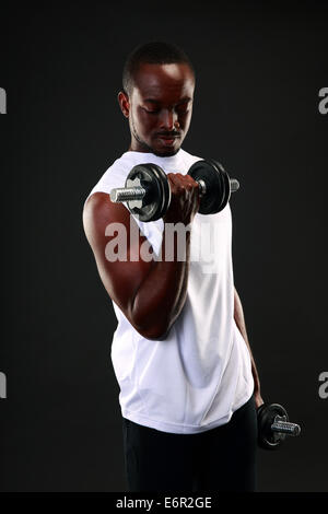 Portrait of african man working out with dumbbells - Stock Photo