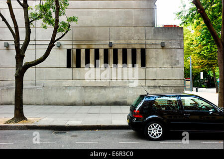 Concrete building window and parked car - Stock Photo