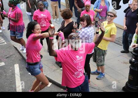 Senoir Black Man at Notting Hill carnival Having pink paint poured on him - Stock Photo