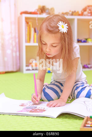 Cute little girl sitting on the floor and drawing picture to the album, having fun at home, happy childhood, having - Stock Photo