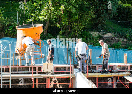 workers at construction site pouring concrete in form - Stock Photo