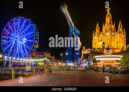 Tibidabo amusement park by night with Temple de Sagrat Cor behind, Barcelona, Catalonia, Spain - Stock Photo