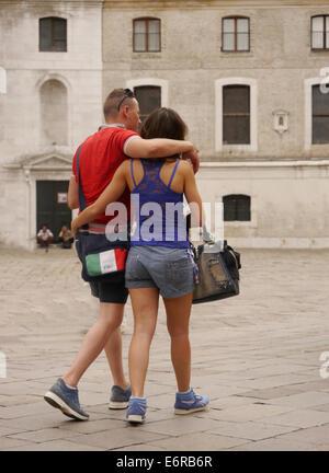 A couple walking along a street in Venice - Stock Photo