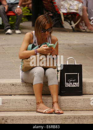 A young woman sitting on a step in the sun looking at her mobile phone with  shopping bag in Venice - Stock Photo