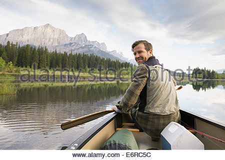 Man sitting in canoe in still lake - Stock Photo