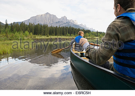 Father and son rowing canoe in still lake - Stock Photo