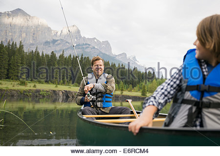 Father and son fishing in canoe in lake - Stock Photo