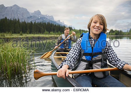 Father and son rowing canoe in lake - Stock Photo