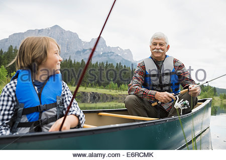 Older man and grandson fishing in lake - Stock Photo