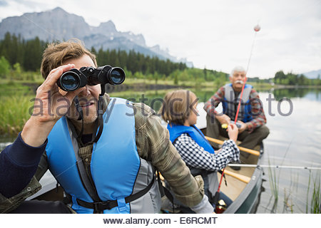 Three generations of men fishing in lake - Stock Photo