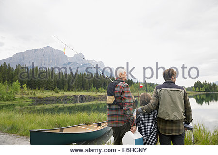 Three generations of men overlooking still lake - Stock Photo