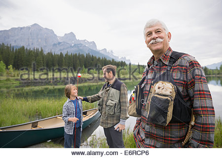 Three generations of men standing by still lake - Stock Photo
