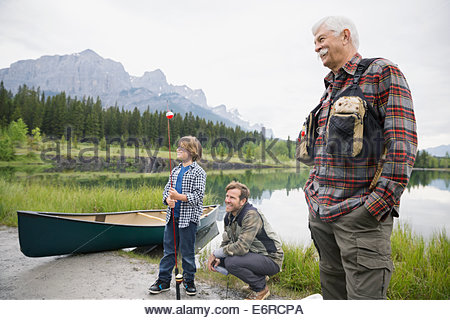Three generations of men by still lake - Stock Photo
