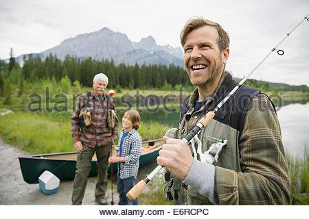 Three generations of men standing by still lake - Stock Photo