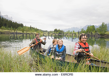 Family rowing canoe in still lake - Stock Photo