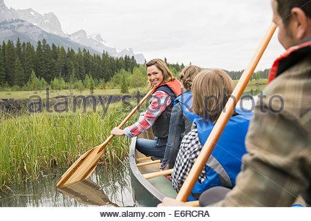 Family rowing canoe in still lake - Stock Photo