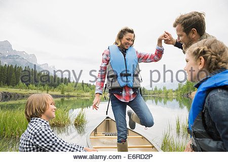 Husband helping wife from canoe in still lake - Stock Photo