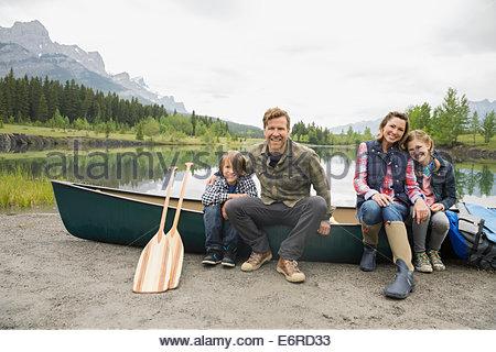 Family sitting by canoe by still lake - Stock Photo