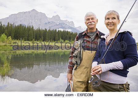 Older couple fishing in still lake - Stock Photo