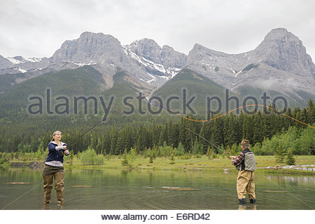 Older couple fishing in still lake - Stock Photo
