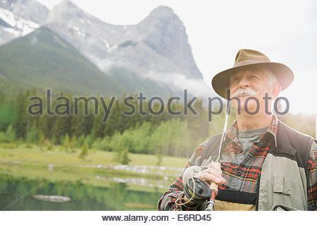 Older man fishing in still lake - Stock Photo