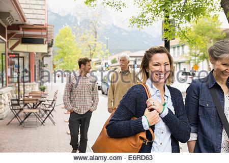 Couples walking on village street - Stock Photo