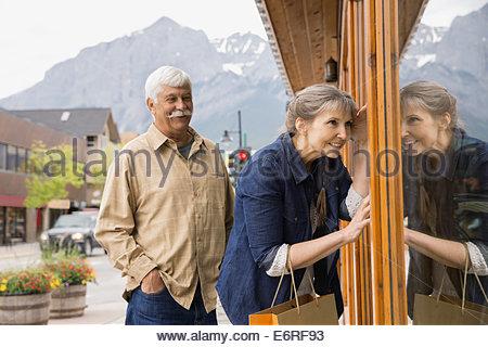 Older couple window shopping on village street - Stock Photo