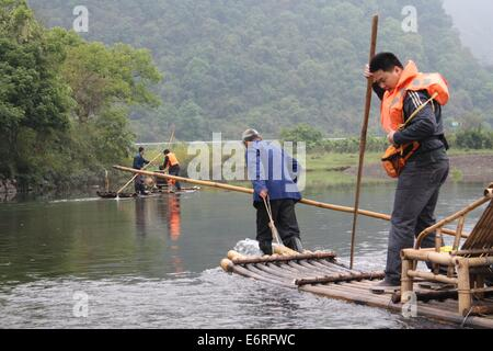 Local fishermen take tourists on a bamboo raft cruise along the Yulong River in China - Stock Photo