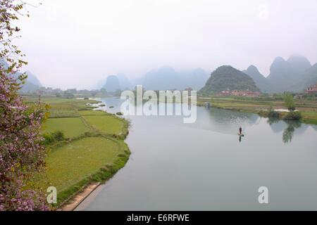 Fisherman going up the Yulong River on his raft - Stock Photo