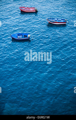 Three small fishing boats with oars and outboard motors are anchored in the bay of Câmara de Lobos. - Stock Photo
