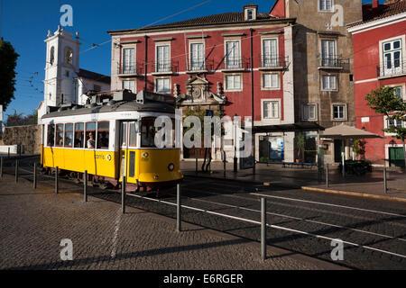 A yellow number 28 tram on Largo das Portas do Sol in Alfama, Lisbon. - Stock Photo