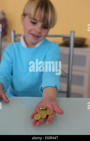 Little boy holding coins - Stock Photo