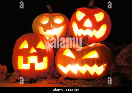 Group of Halloween Jack o Lanterns lit up at night - Stock Photo