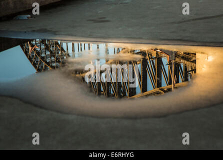 The Sydney Harbour Bridge reflected in a puddle after a heavy rain. - Stock Photo