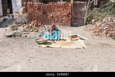 Local woman sitting on the roadside, working sifting grain, in a village near Deogarh, Rajasthan, India - Stock Photo